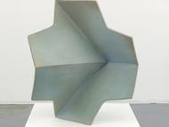 A sculpture of dull green-gray metal, shaped like...